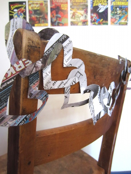 Intertwined newspaper hearts decorating a chair