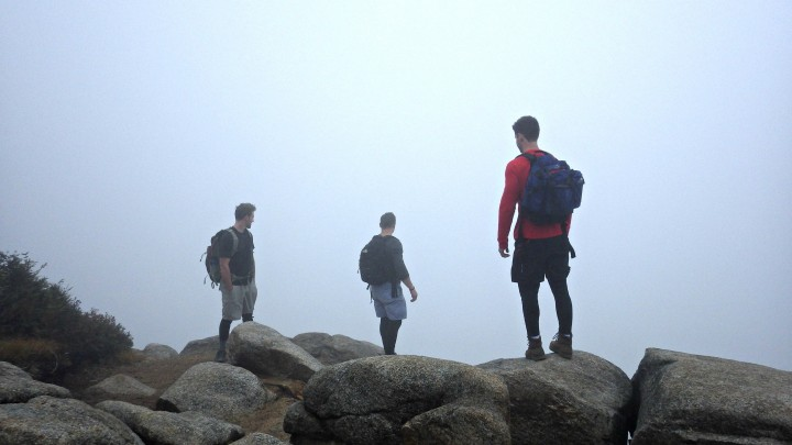 Hikers Ken Carr, Tony Quintilliani, and Brian Briggs stare into the foggy abyss from the same scenic viewpoint in previous picture.