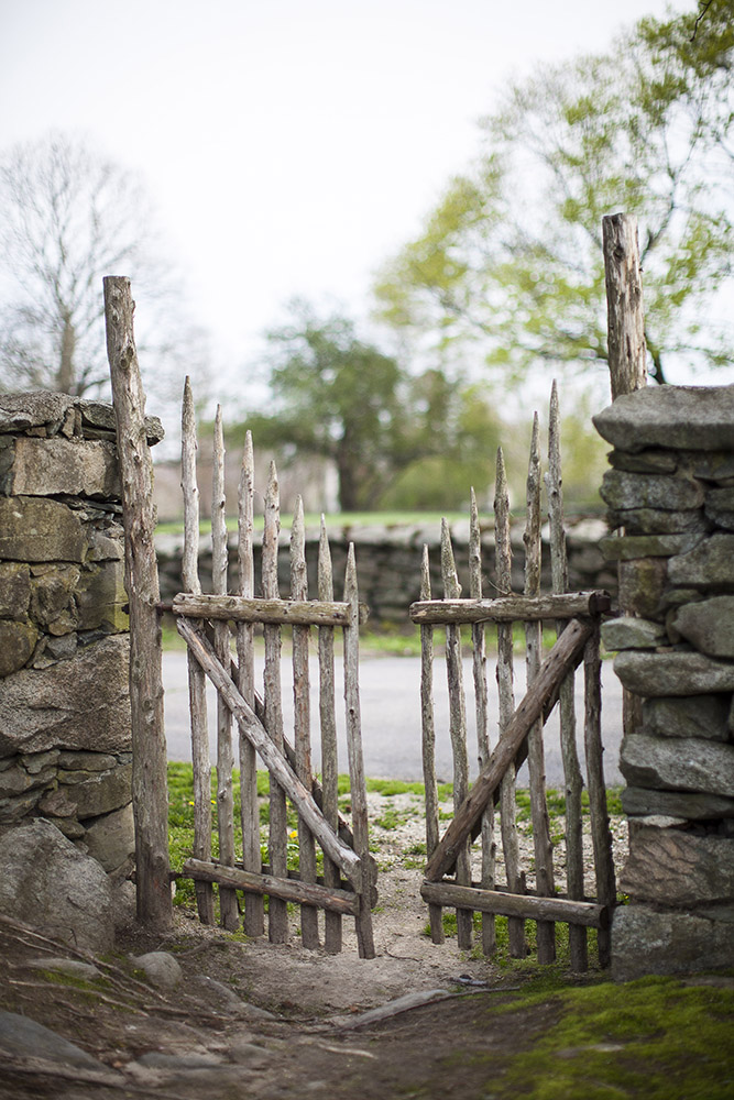 A wooden gate leads to fields and stone walls at Mt. Hope Farm in tk.