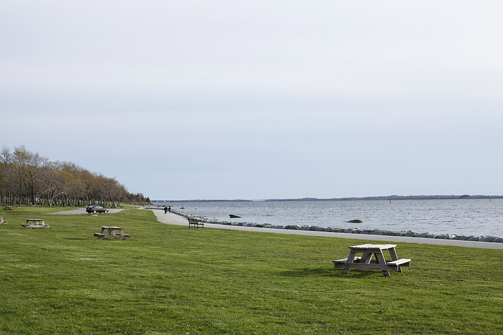 Picnic tables line the walkway along Narragansett Bay at Colt State Park in Bristol.