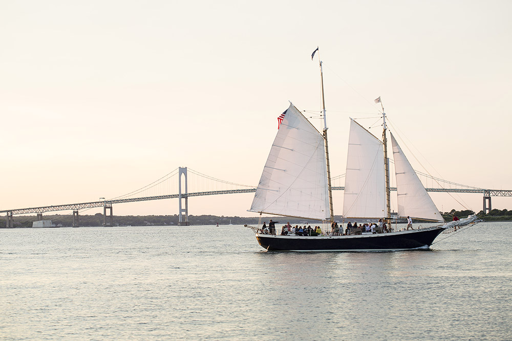 Under sail in Narragansett Bay's quiet waters early in the season with the iconic Claiborne Pell Newport Bridge in the distance.