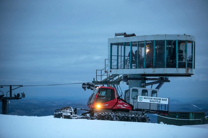 The Motor Room Bar snowcat waits outside of the floor-to-ceiling windowed room while guests enjoy cocktails and d'oeuvres.