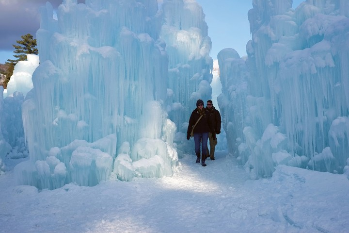 Towering walls of ice dwarf a young couple.