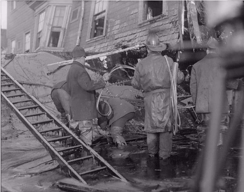 Firemen standing in thick molasses after the disaster.