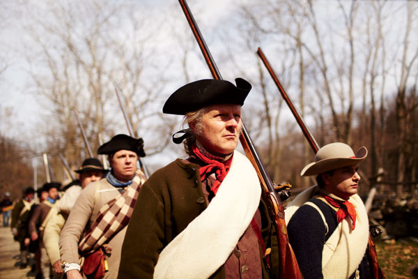 Patriot reenactors march toward Hartwell Tavern in Lincoln.