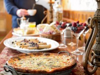 A long table overflows with morning treats, including lemon crepes and tomato and basil breakfast pie.