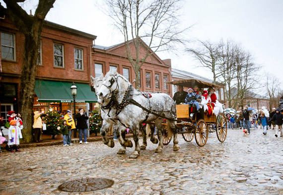 santa and mrs clause make their way along main street the old fashioned way
